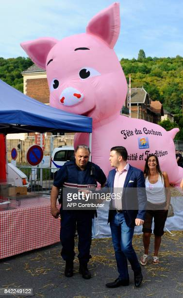 Farright National Front party mayor of Hayange Fabien Engelmann walks past a giant inflatable pig during the party's 'Pig Fest' or 'La fete du...