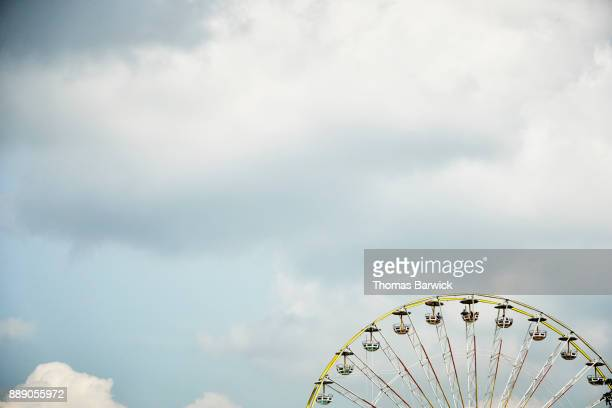 Farris wheel against cloudy sky on summer afternoon