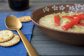 Farro grain soup dressed with red peppers and service in a brown ceramic bowl with a blue napkin and gold sppon and crackers