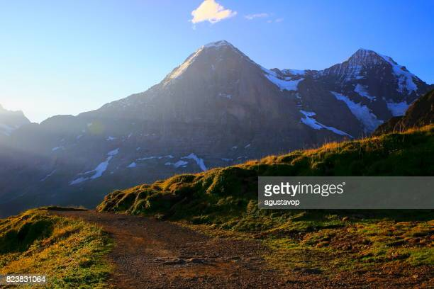 Fary tale landscape: Monch and Eiger view from hiking trail path above idyllic Grindelwald alpine valley and meadows, dramatic swiss snowcapped alps, idyllic countryside, Bernese Oberland,Swiss Alps, Switzerland
