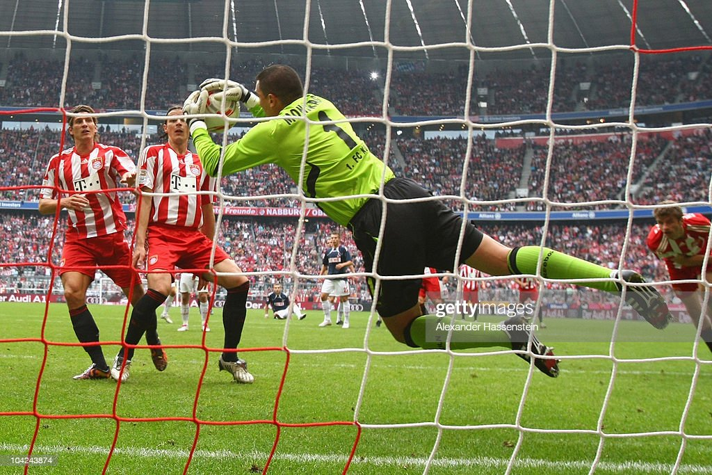 Faryd Mondragon, keeper of Koeln safes a header from Thomas Mueller (R) of Muenchen, whilst <a gi-track='captionPersonalityLinkClicked' href=/galleries/search?phrase=Mario+Gomez+-+Calciatore&family=editorial&specificpeople=635161 ng-click='$event.stopPropagation()'>Mario Gomez</a> (L) of Muenchen and his team mate Daniel van Buyten looks on during the Bundesliga match between FC Bayern Muenchen and 1. FC Koeln at Allianz Arena on September 18, 2010 in Munich, Germany.