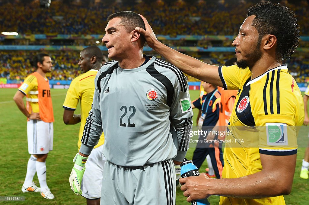 Faryd Mondragon (L) of Colombia is congratulated by his teammate Carlos Valdes after the 4-1 win in the 2014 FIFA World Cup Brazil Group C match between Japan and Colombia at Arena Pantanal on June 24, 2014 in Cuiaba, Brazil.