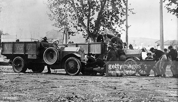 A fascist action squad hidden between two trucks getting ready to attack some socialists Rome 1921