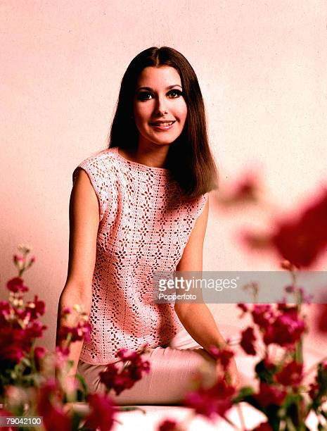Fashion 1960's A smiling young woman surrounded by deep pink flowers is wearing a sleeveless pastel pink laceknit top