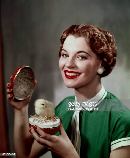 Fashion 1960's A young woman with a neat short wave hairstyle holds open a festive Easter egg in which a live chick is standing