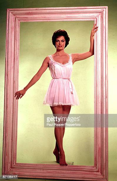 Fashion 1960's Full length portrait of a model wearing a pale pink baby doll negligee while standing inside an oversized picture frame