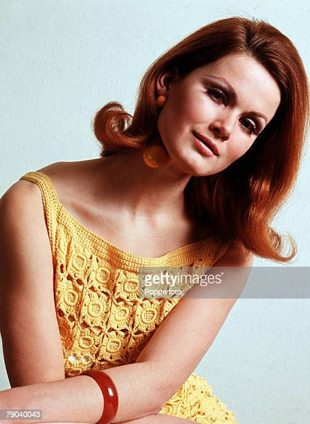 Fashion 1960s Knitwear A glamorous woman with shoulder length auburn hair wears a delicately crocheted sleeveless dress in Primrose yellow