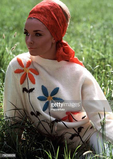 Fashion 1966 Knitwear A model with fashionably heavy make up and a bee hive hairstyle wrapped in a headscarf sits in long grass wearing a knitted...