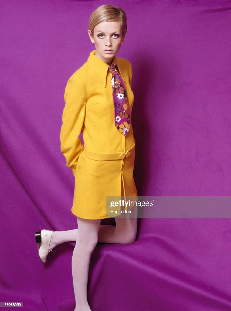 Fashion, 1967 A portrait of the model Twiggy wearing a fashionable yellow collared outfit with a multi-coloured floral tie, posing for the camera in a studio against a brightly coloured purple backdrop