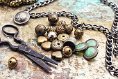 Metal beads,buttons,chain and scissors on retro background