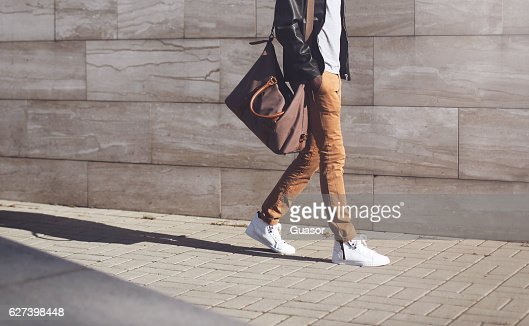 Fashion african man in black jacket walking in city : Photo