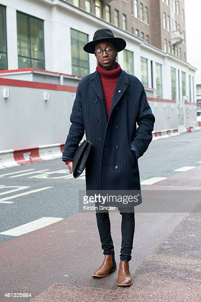 Fashion and celebrity stylist Jay Xyyx wearing an H and M hat villain coat Topman jeans and boots clutch bag and glasses from a vintage boutique on...