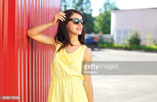 Fashion beautiful woman wearing yellow dress and sunglasses in city : Stock Photo