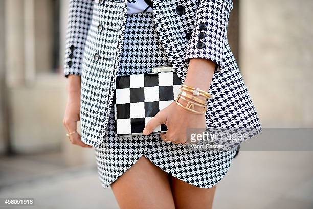 Fashion blogger Aimee Song poses wearing a Jaggar jacket and skirt and Kate Spade clutch on September 24 2014 in Paris France