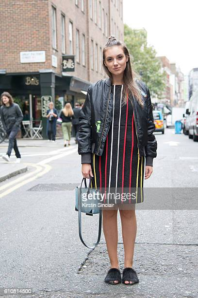 Fashion blogger Andreea Cristea wears a Daisy Street jacket Moon Lee dress Helmer bag and custom made shoes on day 5 of London Womens Fashion Week...