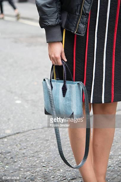 Fashion blogger Andreea Cristea wears a Daisy Street jacket Moon Lee dress and Helmer bag on day 5 of London Womens Fashion Week Spring/Summer 2016...