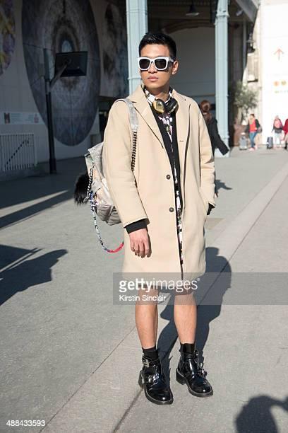 Fashion Blogger Bryan Boy wears a Chanel backpack Headphones by Frends Balenciaga sunglasses and shoes Givenchy shirt and shorts Balenciaga black...
