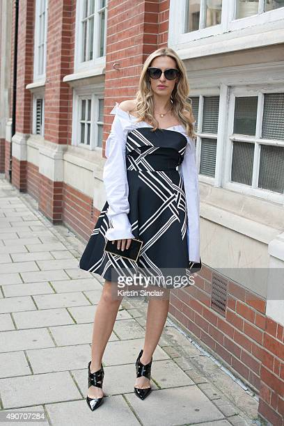 Fashion Blogger Camila Carril wears a Keepsake dress Jimmy Choo sunglasses and shoes and a Reiss bag on day 3 during London Fashion Week...