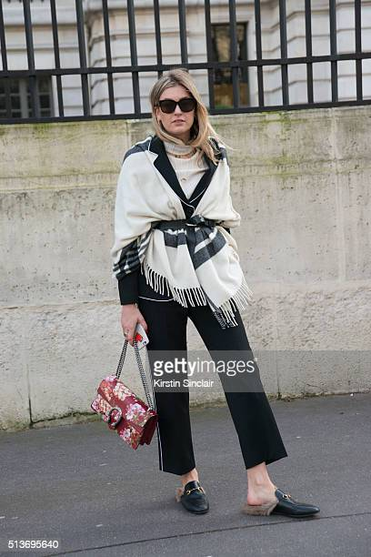 Fashion blogger Camille Charriere wears Gucci top and trousers Acne belt and Celine sunglasses on day 3 during Paris Fashion Week Autumn/Winter...