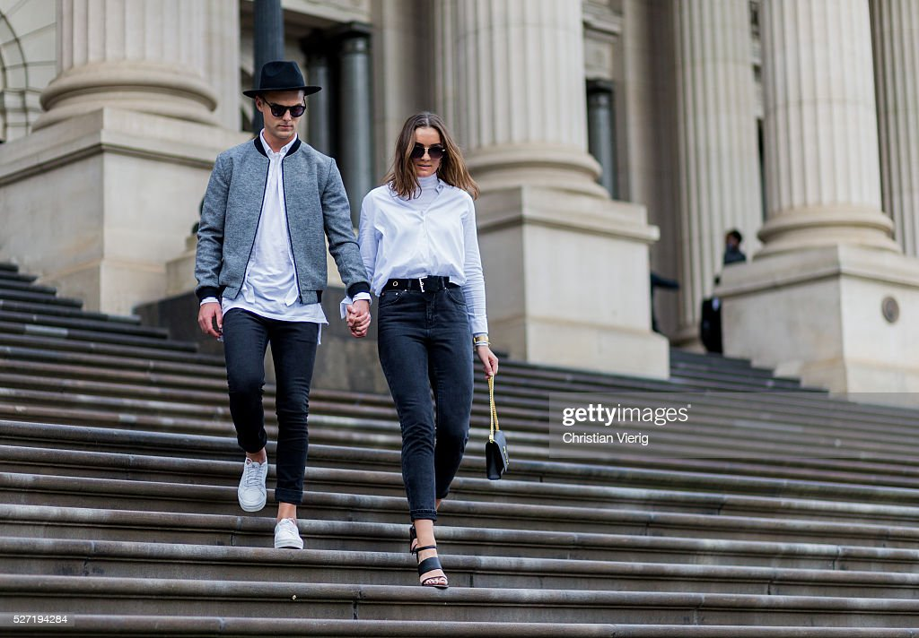 Fashion blogger couple Shaun Lyle wearing a grey Topman college jacket, a black hat and sunglasses, a long white Topman tshirt, black Topman jeans, white Senso sneakers and Holly Titheridge wearing black sunglasses, a white Topshop button shirt, black Topshop denim jeans, black Alias Mae heel sandals, black Yves Saint Laurent bag on May 2, 2016 in Melbourne, Australia