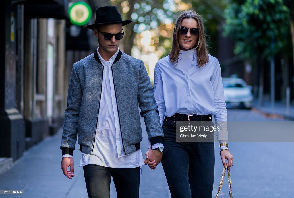 Fashion blogger couple Shaun Lyle wearing a grey Topman college jacket, a black hat and sunglasses, a long white Topman tshirt, black Topman jeans and Holly Titheridge wearing black sunglasses, a white Topshop button shirt, black Topshop denim jeans, black Yves Saint Laurent bag on May 2, 2016 in Melbourne, Australia