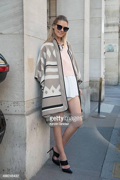 Fashion Blogger Dasha Gold is wearing a Zara poncho Shakuhachi top and shorts Tony Bianco shoes The Bag Department bag HI sunglasses Kittie...