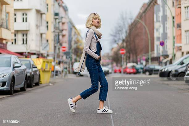 Fashion blogger Ebba Zingmark wearing a dark blue denim jumpsuit an beige scarf and jumper and white Adidas sneaker on March 24 2016 in Berlin Germany