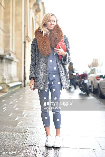 Fashion blogger Elizabeth Minett poses wearing a vintage coat Asilio top and pants Superga shoes and Chanel clutch on Day 1 of Paris Fashion Week...