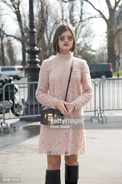 Fashion Blogger Elvira Abasova wears Gucci boots Louis Vuitton bag Ray Ban sunglasses Chanel broach and a Ala Russe Dress look on day 8 during Paris...