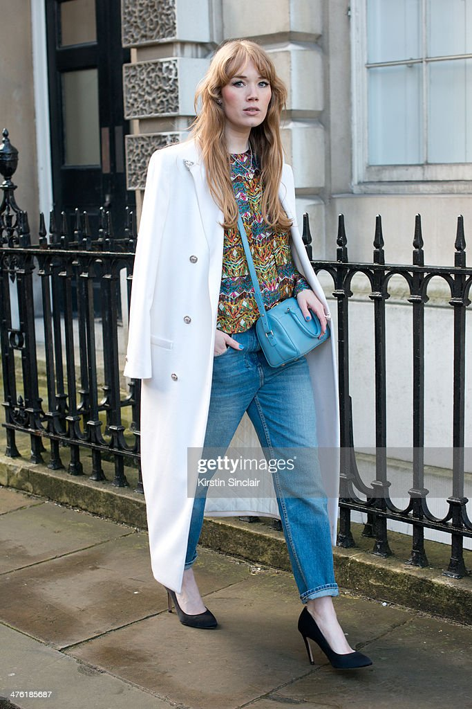 Fashion Blogger Fiona Jane wears a Saint Laurent bag, True Religion jeans, Zara shoes, Won-Hundred top, Versace coat, and Back rings on day 5 of London Collections: Women on February 18, 2014 in London, England.