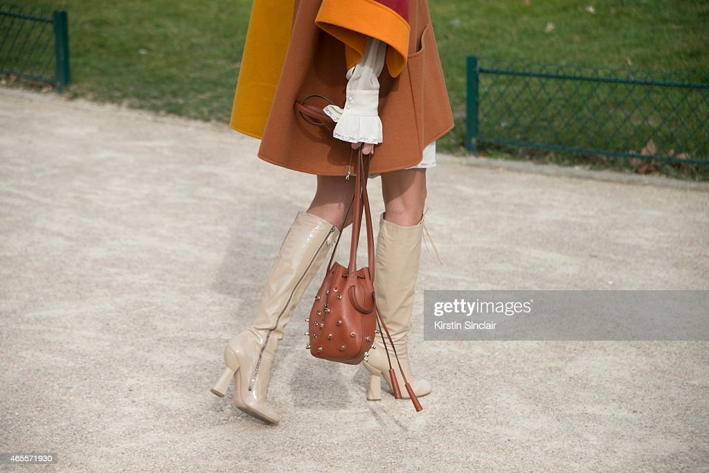 Fashion blogger Helena Bordon wears Miu Miu boots Philosophy cape and dress and a Todâs bags on day 5 of Paris Collections Women on March 07 2015 in...