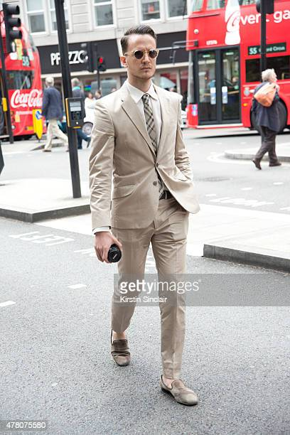 Fashion blogger Henry Balit wears Paul Smith suit Burberry tie Giuseppe Zanotti shoes and Lesca sunglasses on day 4 of London Collections Men on June...