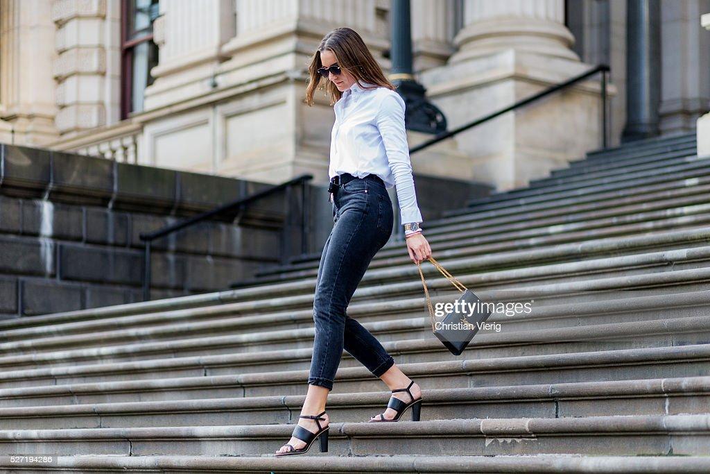 Fashion blogger Holly Titheridge wearing black sunglasses, a white Topshop button shirt, black Topshop denim jeans, black Alias Mae heel sandals, black Yves Saint Laurent bag on May 2, 2016 in Melbourne, Australia