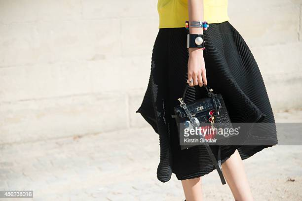 Fashion Blogger Irene Kim is wearing a Issey Miyake skirt Fendi bag and Barney's Fork and Chanel bracelet on day 4 of Paris Collections Women on...