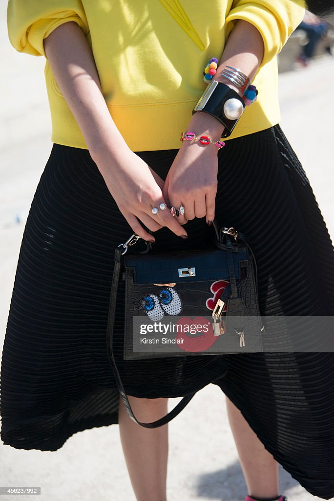 Fashion Blogger Irene Kim is wearing a Lucky Chouette top Issey Miyake skirt Fendi bag Barney's Fork and Chanel bracelets and Chanel sunglasses on...