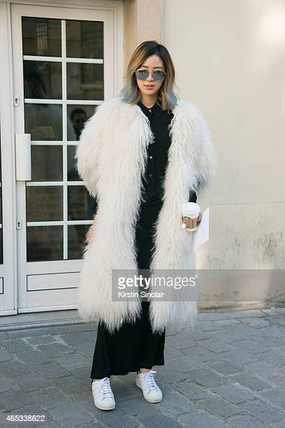 Fashion blogger Irene Kim wears Thomas Wylde fur coat Ann Demeulemeester dress and Adidas shoes on day 3 of Paris Collections Women on March 05 2015...