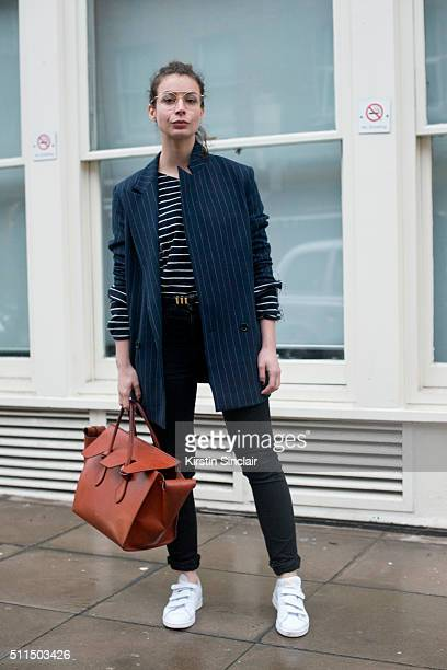 Fashion Blogger Irina Lakicevic wears a Ganni jacket Saint Laurent jeans and belt Celine top and bag and Adidas shoes on day 2 during London Fashion...