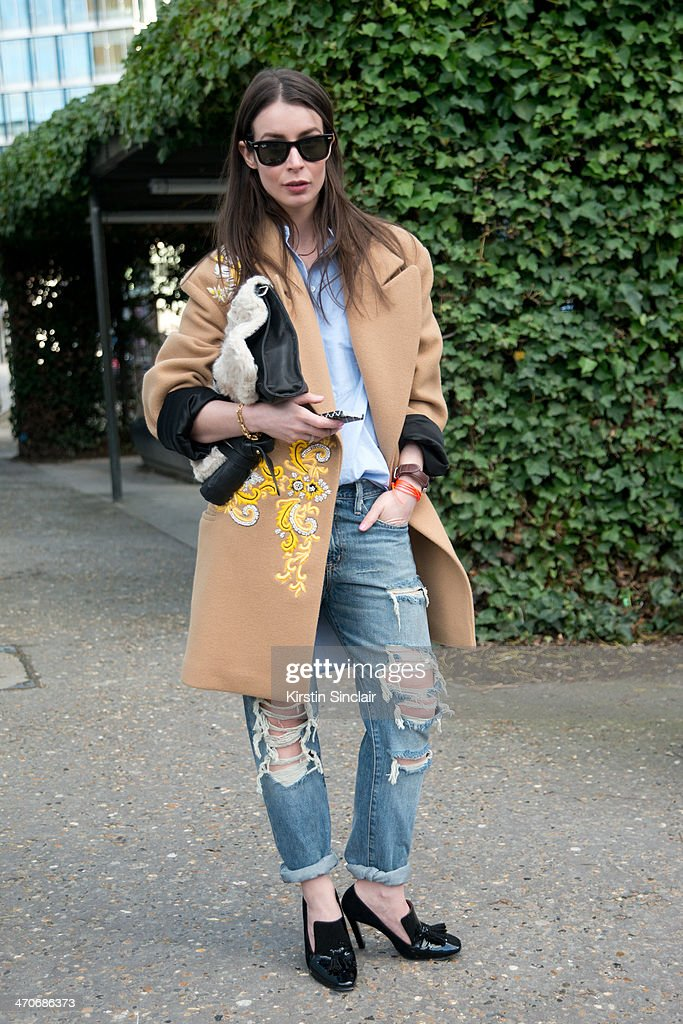 Fashion Blogger Irina Lakicevic wears Ray Ban sunglasses, Little Liffner bag, By Malene Birger shirt, Ralph Lauren jeans, Celine shoes, Dries Van Noten coat on day 3 of London Collections: Women on February 16, 2014 in London, England.