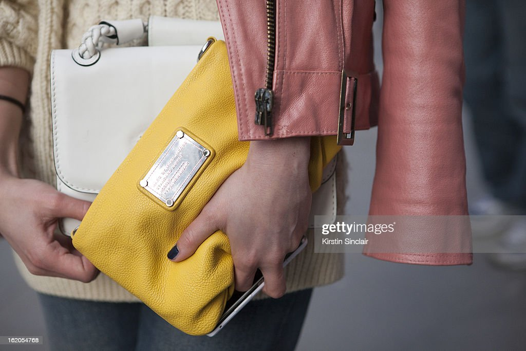 Fashion Blogger Irina Lakicevic wears vintage jacket and jumper, Acne jeans, white purse by Valentino and yellow clutch by Marc by Marc Jacobs on day 4 of London Womens Fashion Week Autumn/Winter 2013 on February 16, 2013 in London, England.