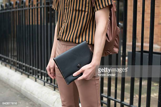 Fashion blogger Jocelyn Yih wears a Topman shirt Acne trousers and Rucksack and a Coach clutch bag on day 4 of London Collections Men on June 13 2016...