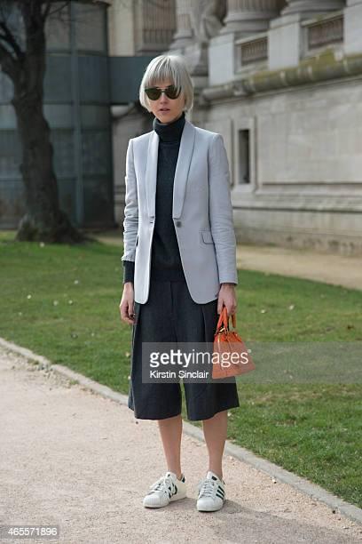 Fashion Blogger Linda Tol wears Louis Vuitton bag LK Bennett jacket Dries Van Noten trousers Uniqlo sweater Adidas shoes and Mykita sunglasses on day...