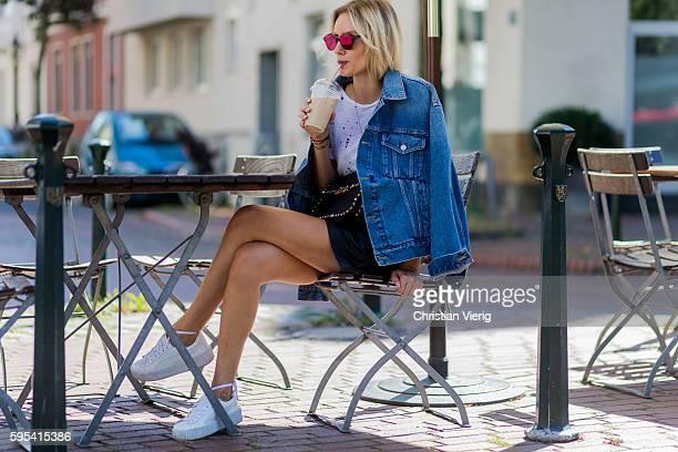 Fashion blogger Lisa Hahnbueck drinking an Iced Coffee wearing blue denim Balenciaga Jeans jacket black Set Leather Shorts white Iro TShirt white...