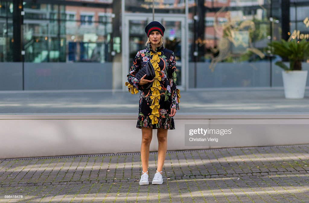 Fashion blogger Lisa Hahnbueck wearing a Gucci Silk Dress with yellow bows and floral print white Puma Fenty Sneaker Gucci wool cap black Chanel Boy...