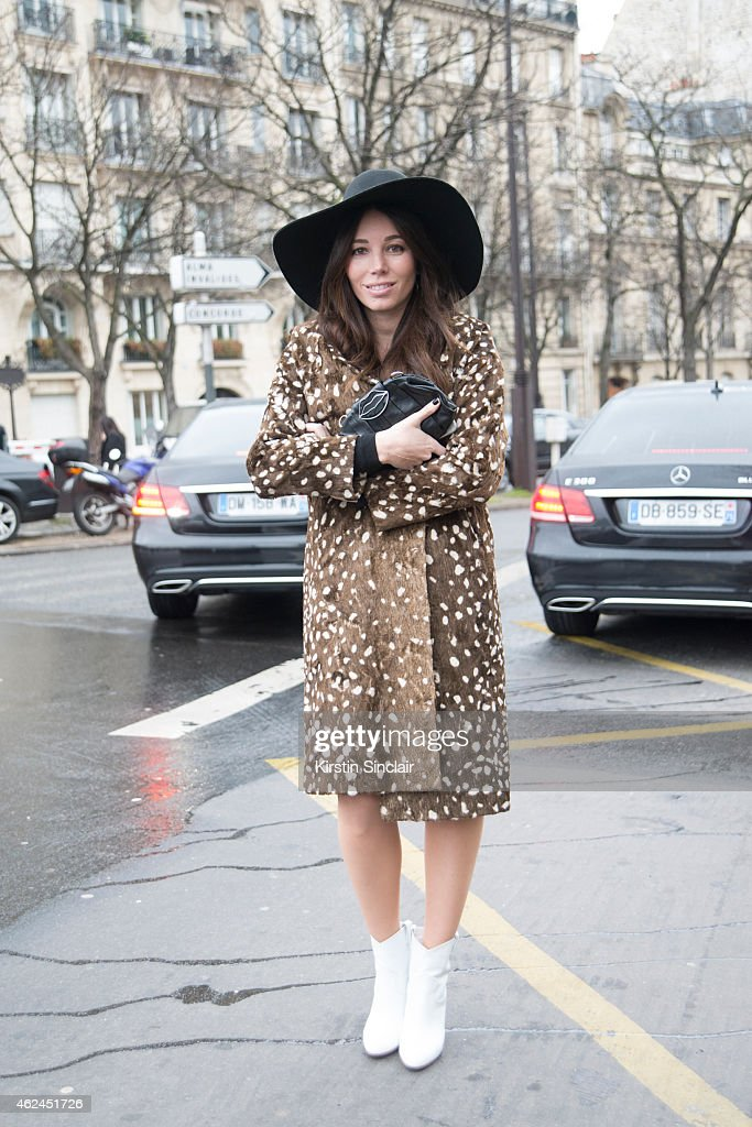 Fashion blogger Natacha Steven wears a Prada clutch Topshop hat and coat and Gianvito Rossi boots on day 4 of Paris Haute Couture Fashion Week...
