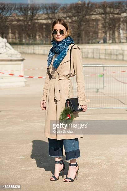Fashion blogger Noor De Grout wears Ray Ban sunglasses Justice trench coat HM trousers ASOS shoes and Other stories bag on day 3 of Paris Collections...