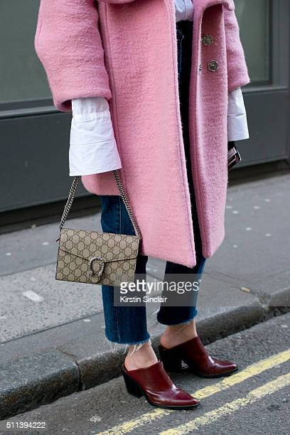 Fashion blogger Olivia Kijo wears a Hanger coat Gucci bag Zara shoes and Levi's jeans on day 1 during London Fashion Week Autumn/Winter 2016/17 on...