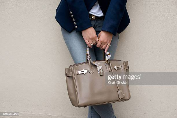 Fashion Blogger Peony Lim is wearing a Hermes bag H and M jeans Balmain jacket and Gap shirt on day 2 of London Collections Women on September 13...