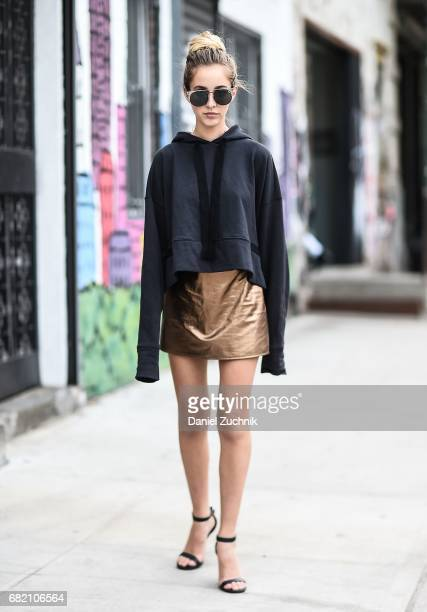 Fashion Blogger Rosa Crespo is seen in Noho wearing a Nude jumper Matel gold skirt YSL heels and Quay sunglasses on May 11 2017 in New York City
