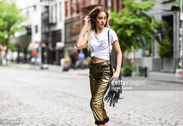 Fashion Blogger Rosa Crespo is seen in Noho wearing an Iorane World tshirt Nude gold pants and Salar Milano bag on May 11 2017 in New York City