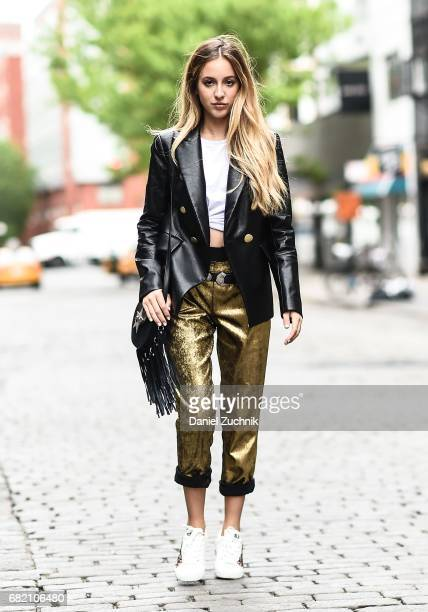Fashion Blogger Rosa Crespo is seen in Noho wearing an Iorane World tshirt Nude black jacket Nude gold pants Ash sneakers and Salar Milano bag on May...